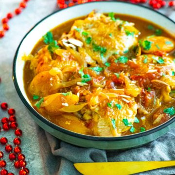 Chicken tagine in a bowl next to a string of red beads