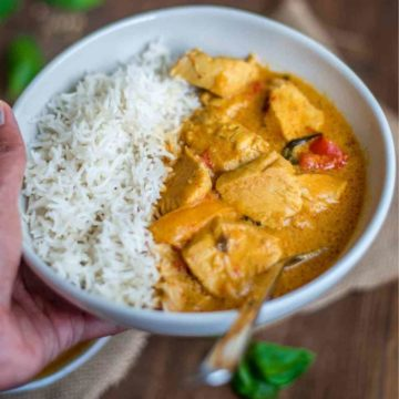 Hand holding a bowl of Thai chicken curry and rice