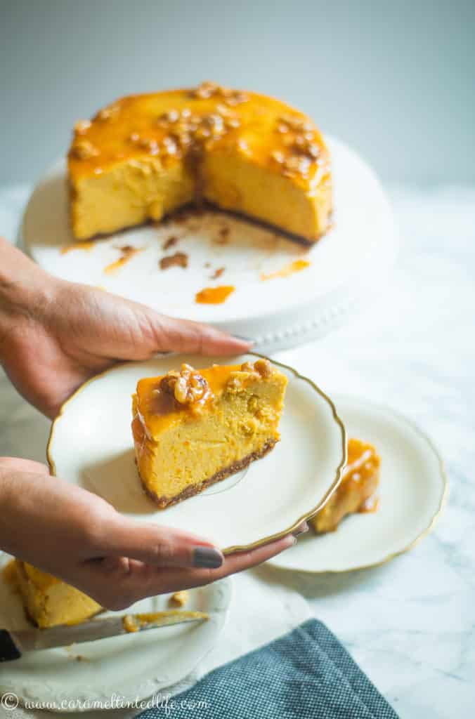 A single slice of Pumpkin Cheesecake on a plate, held by two hands