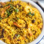 Shrimp and rice with coriander and raisins on a white plate