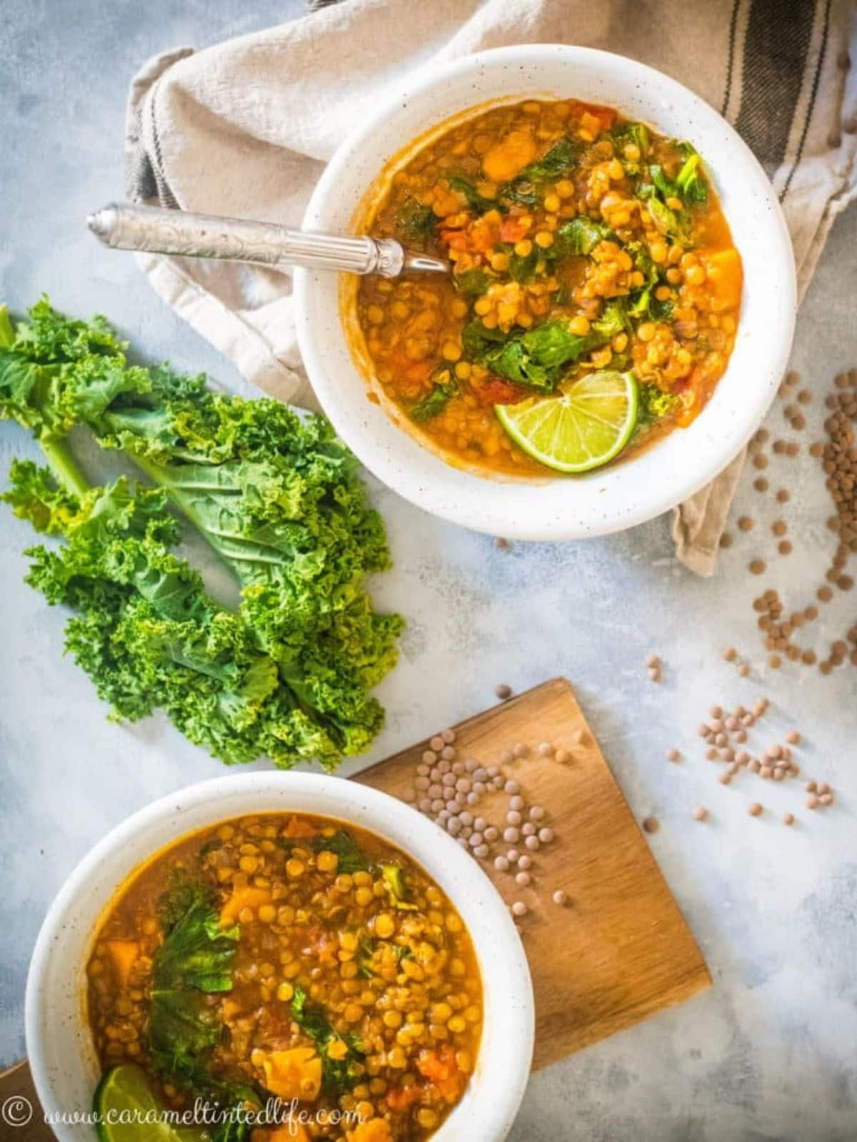 Two while bowls of lentil soup on a table with kale and raw lentils in the background