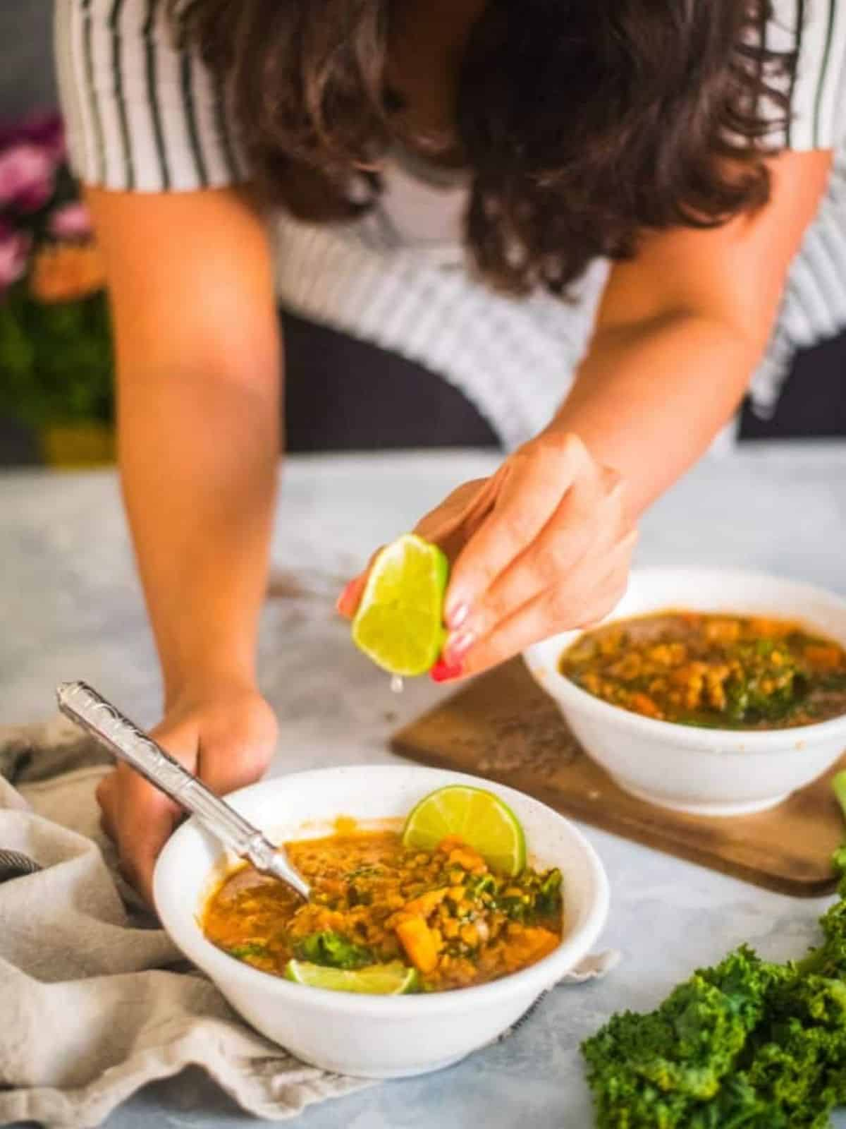 Instant Pot Lentil Soup with Kale and Sweet Potato being served with lime