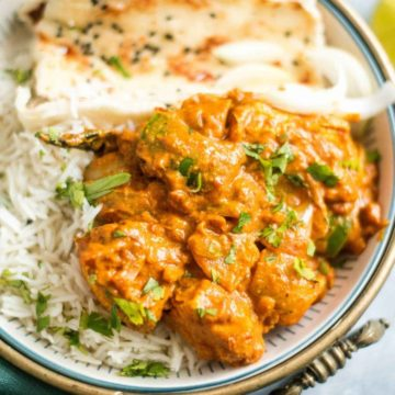 Chicken karahi served in a brass bowl with naan and rice