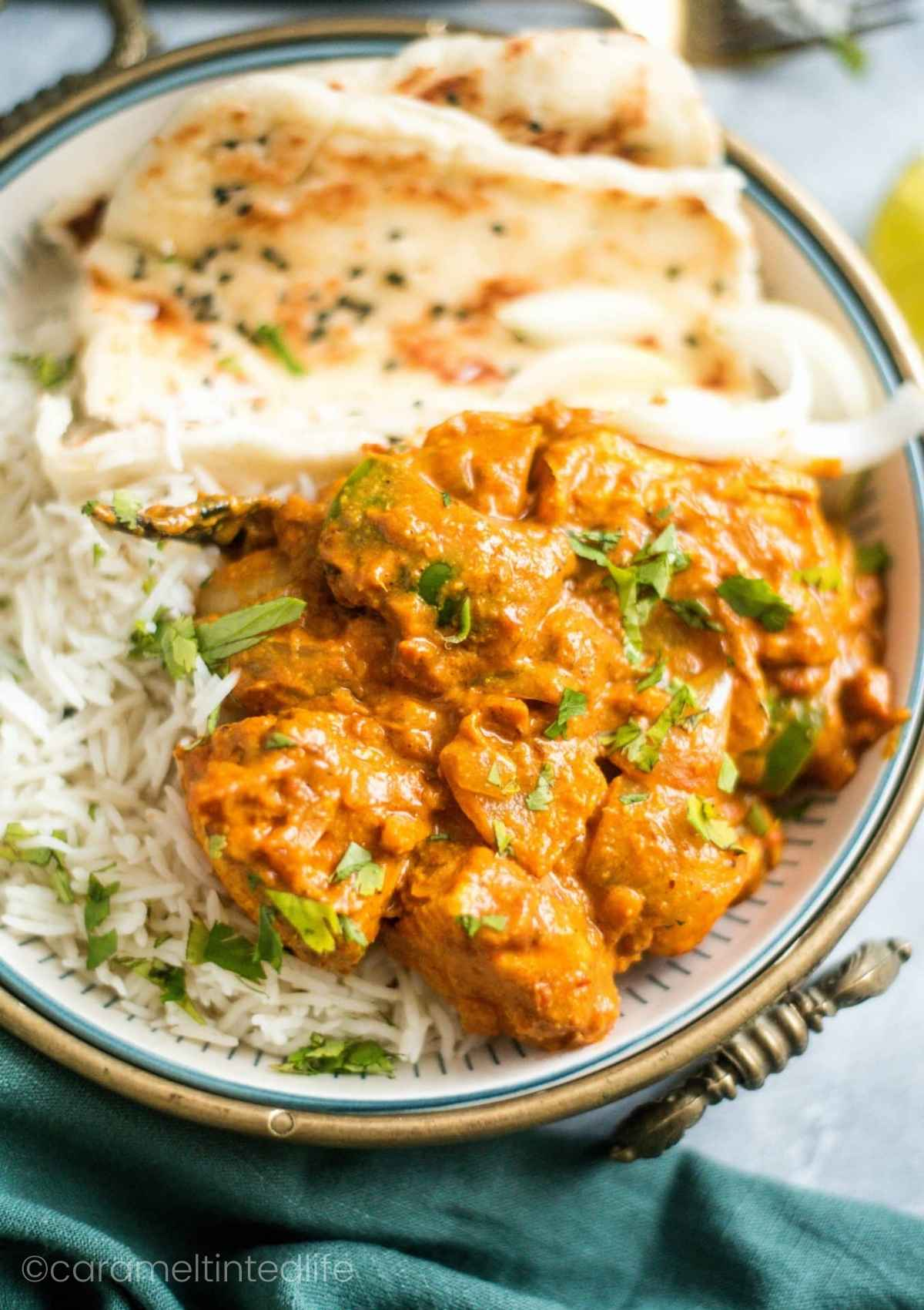 Kadai Chicken in a plate served with rice and naan