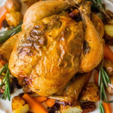 Top view of a whole roast chicken on a bed of roasted vegetables and herbs