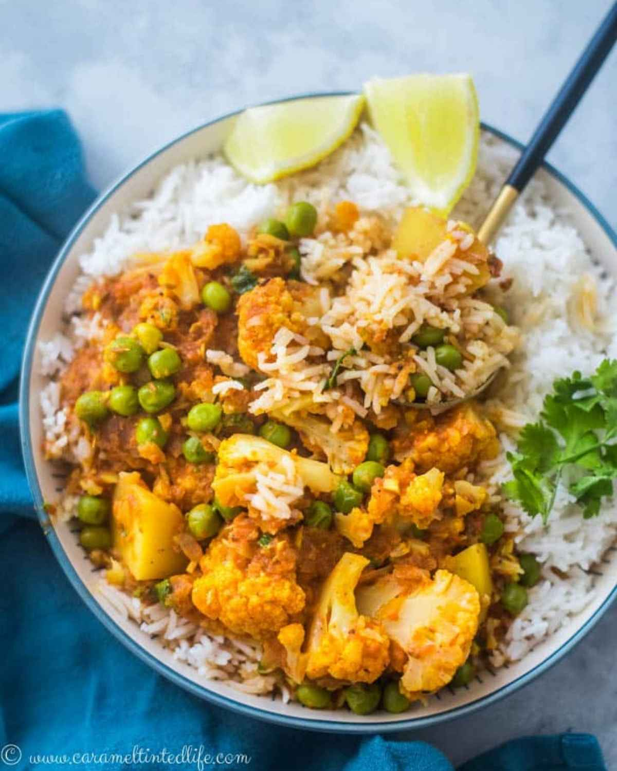 Cauliflower curry served over rice, with a spoon
