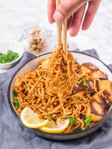 Noodles in a bowl being lifted with chopsticks