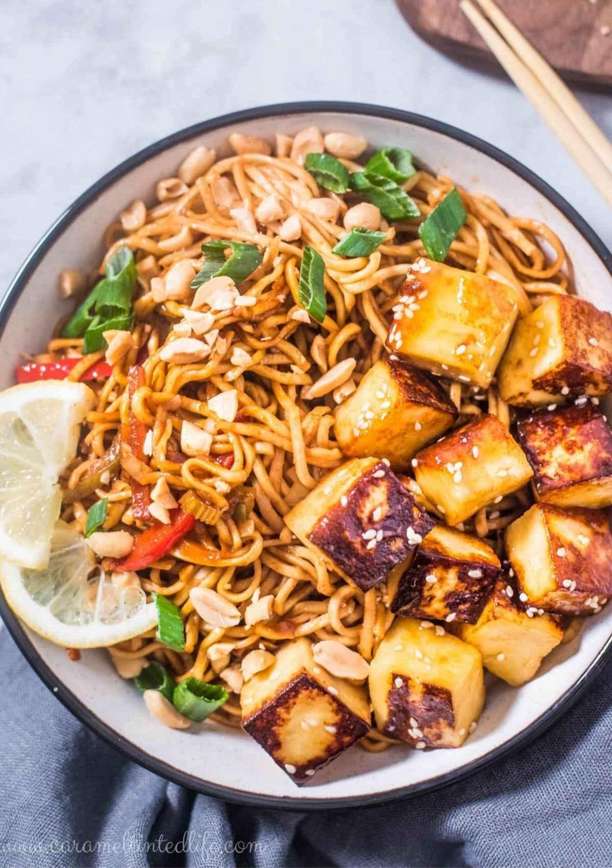 Noodle bowl with noodles, paneer, peanuts, stir-fried veggies