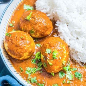 A bowl of egg curry and rice on a plate
