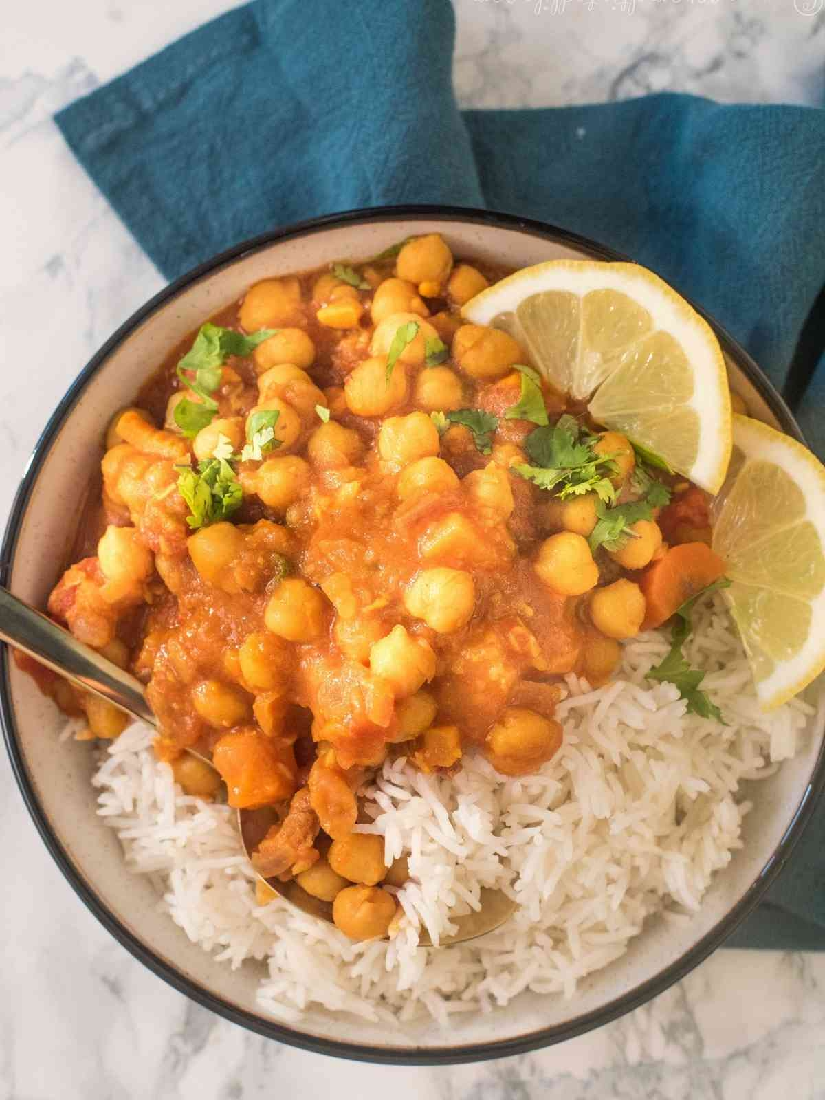 Chickpea tagine served in a bowl with rice and lemon