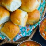 Pav bread on a tray next to pav bhaji