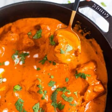 Butter Chicken in a golden spoon held by a hand