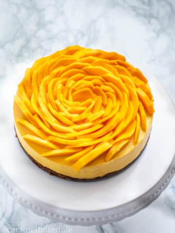 Mango cheesecake with mango slices on top on a cake stand
