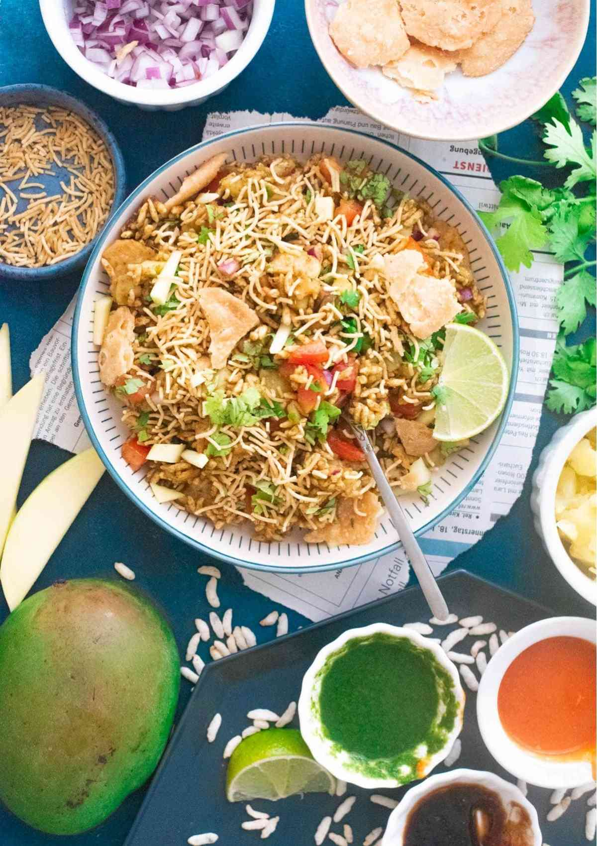 Bhel puri on a plate surrounded by ingredients to make it