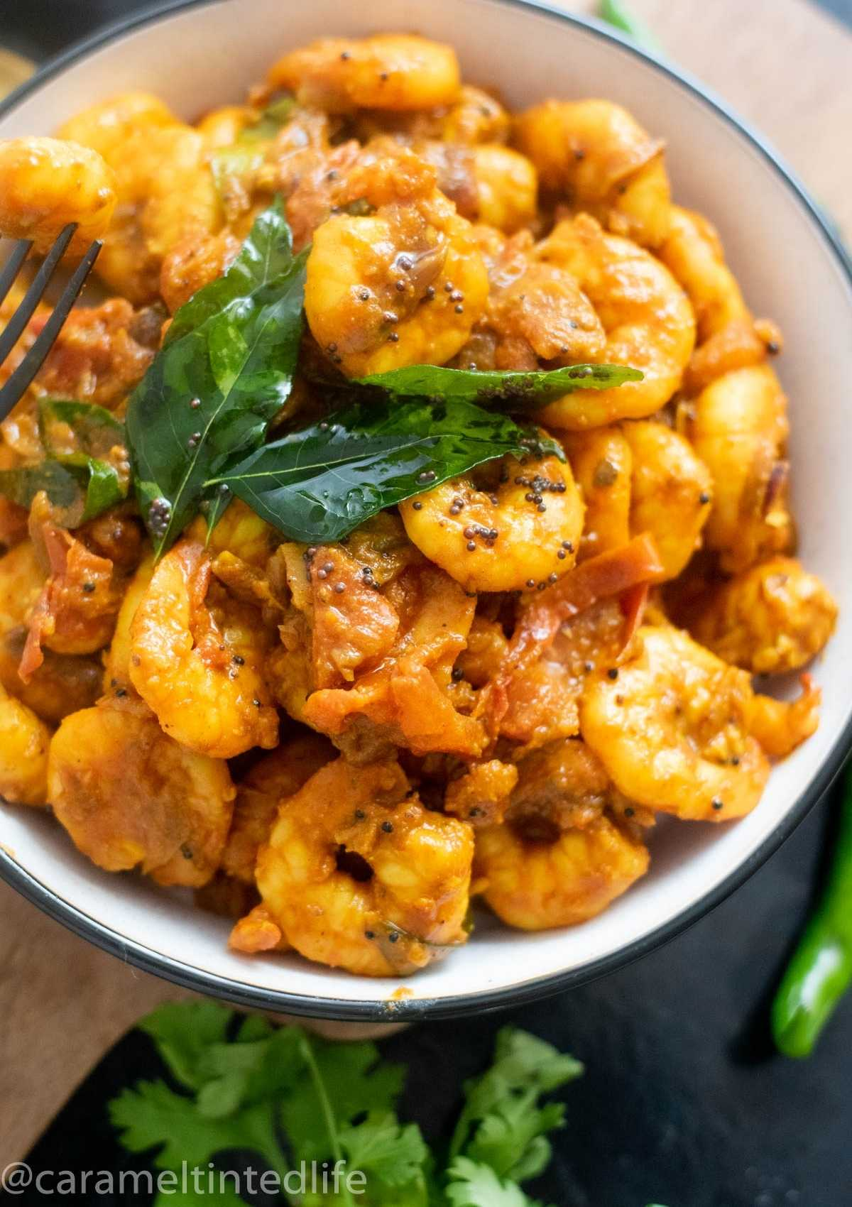 A close-up of shrimp masala tempered with curry leaves in a bowl