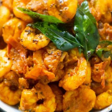Close-up of shrimp masala, curry leaves, mustard seeds in a bowl