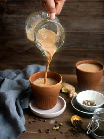 Masala chai being poured into a terracotta cup