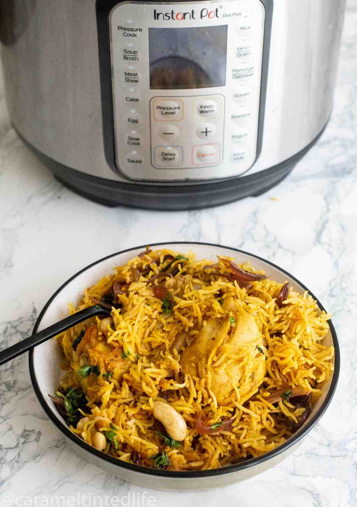 Chicken biryani served in a bowl in front of the Instant Pot