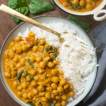 Coconut chickpea curry with spinach in a bowl with rice and a fork