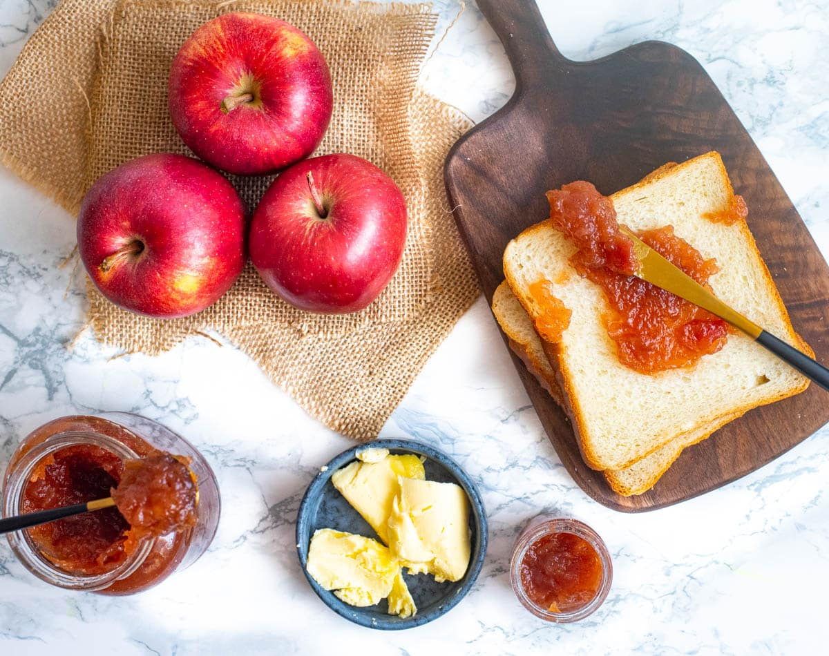 Sandwich bread with apple jam and knife, butter in a dish and apples
