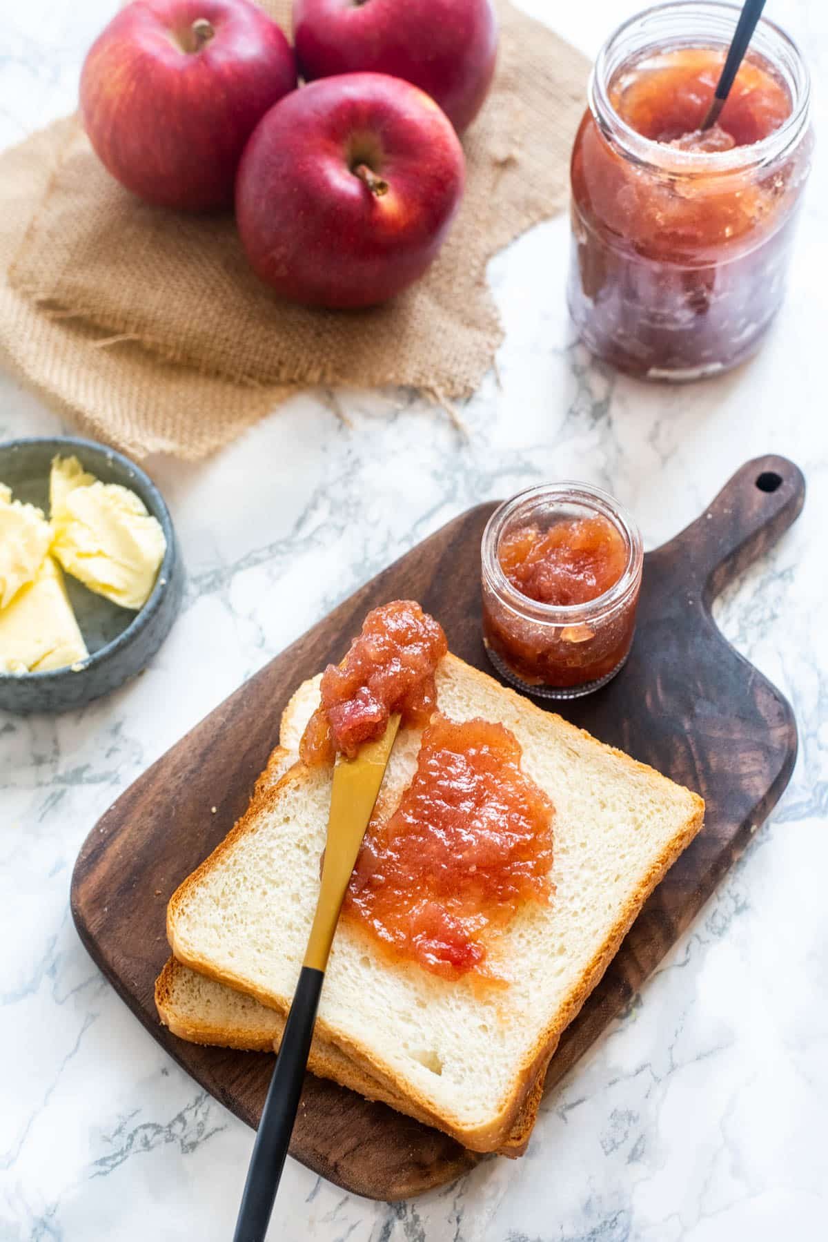 Apple jam spread on sandwich bread with a knife