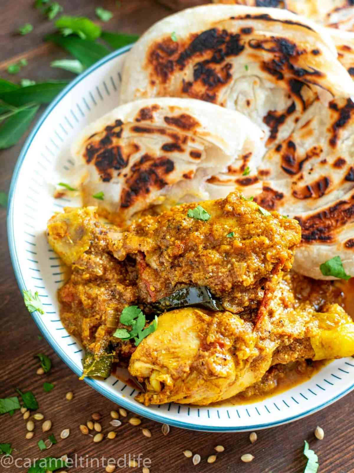 Chicken chettinad curry on a plate with malabar parotta