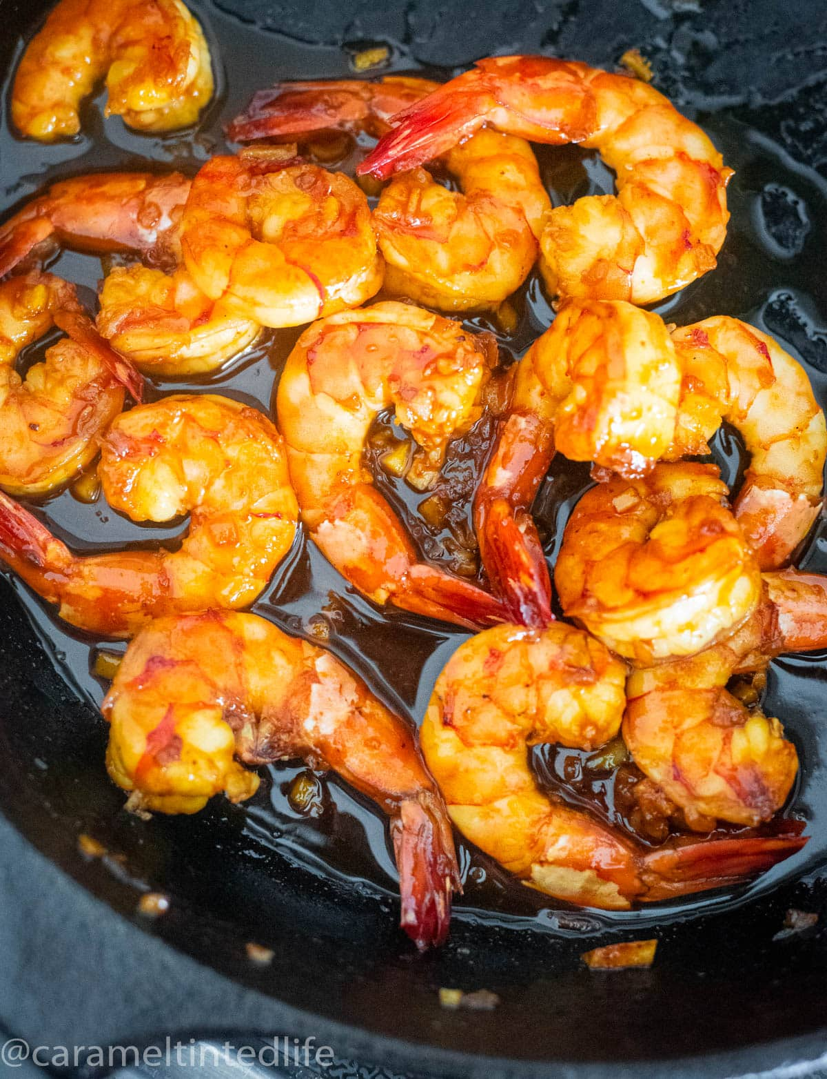Prawns cooking in a honey garlic sauce in a cast iron skillet pan