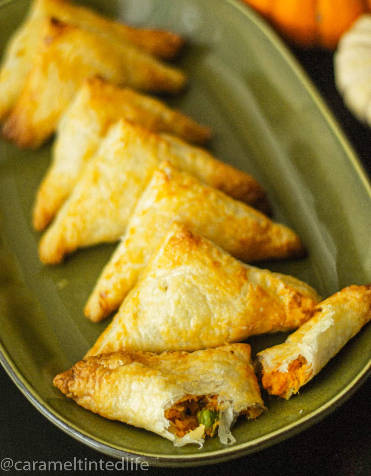 Puff pastry samosas arranged on a green plate