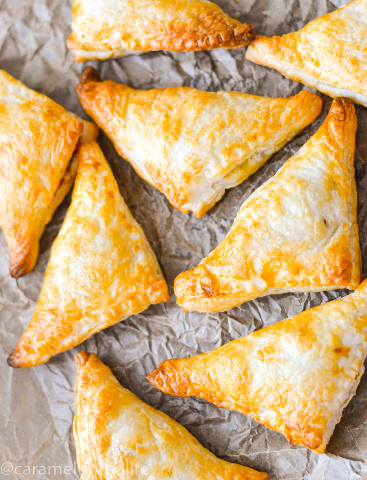 Baked puff pastry samosas on a baking paper