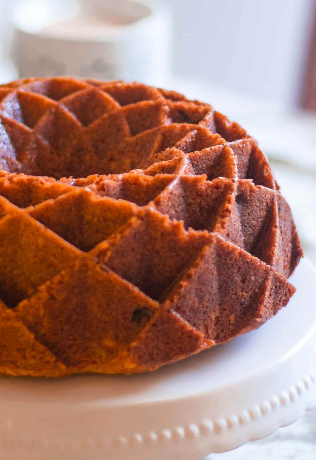 Close-up of apple bundt cake on a white cake stand