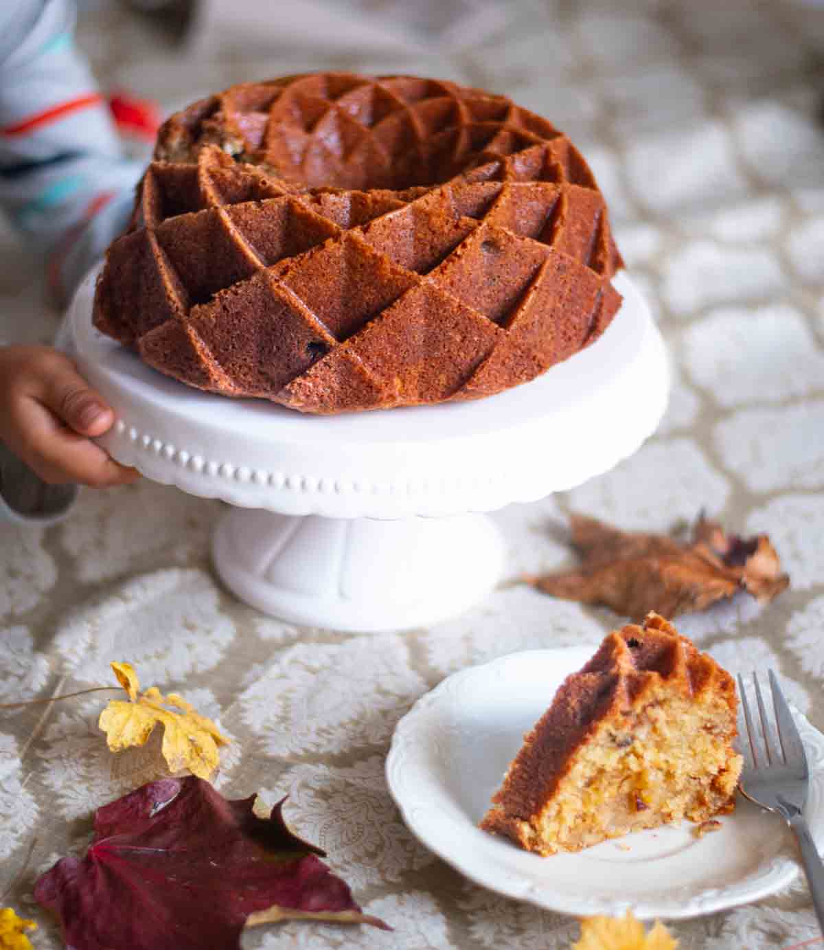 Apple bundt cake on a white cake stand with a single slice on a plate in the foreground