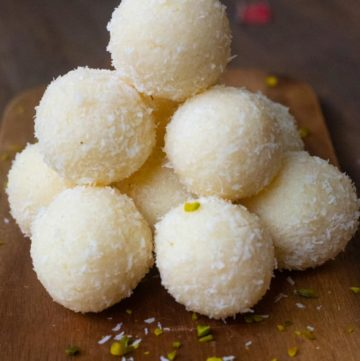 A stack of coconut ladoos piled on a wooden board with scattered pistachios