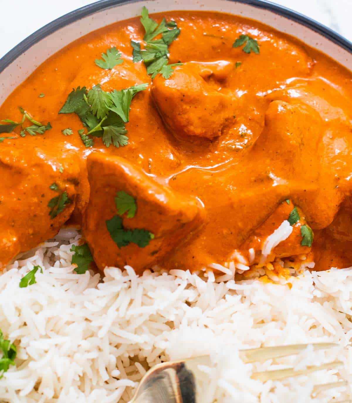 Butter chicken in a bowl with basmati rice and a fork
