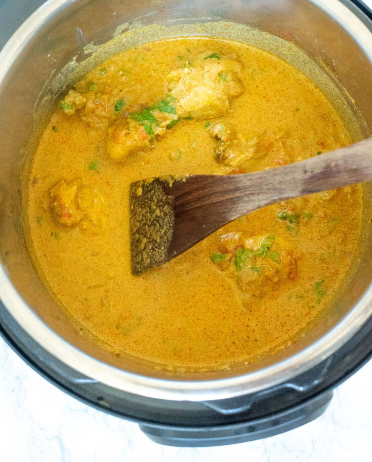 Chicken curry inside the Instant Pot, with a wooden ladle in it