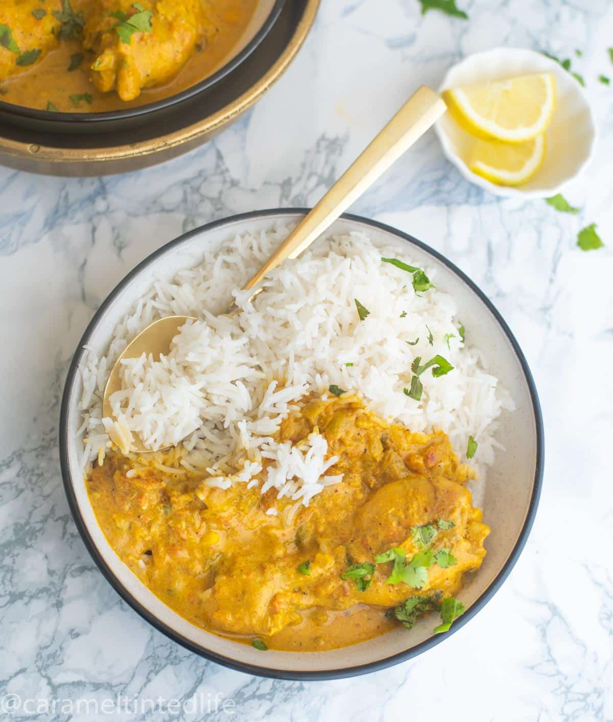 Bowl of white basmati  rice and chicken curry with a spoon in it