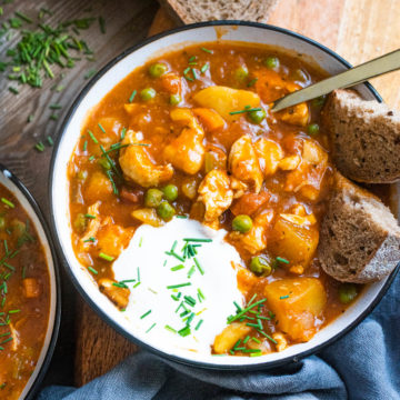 Chicken stew in a bowl with bread and sour cream garnish