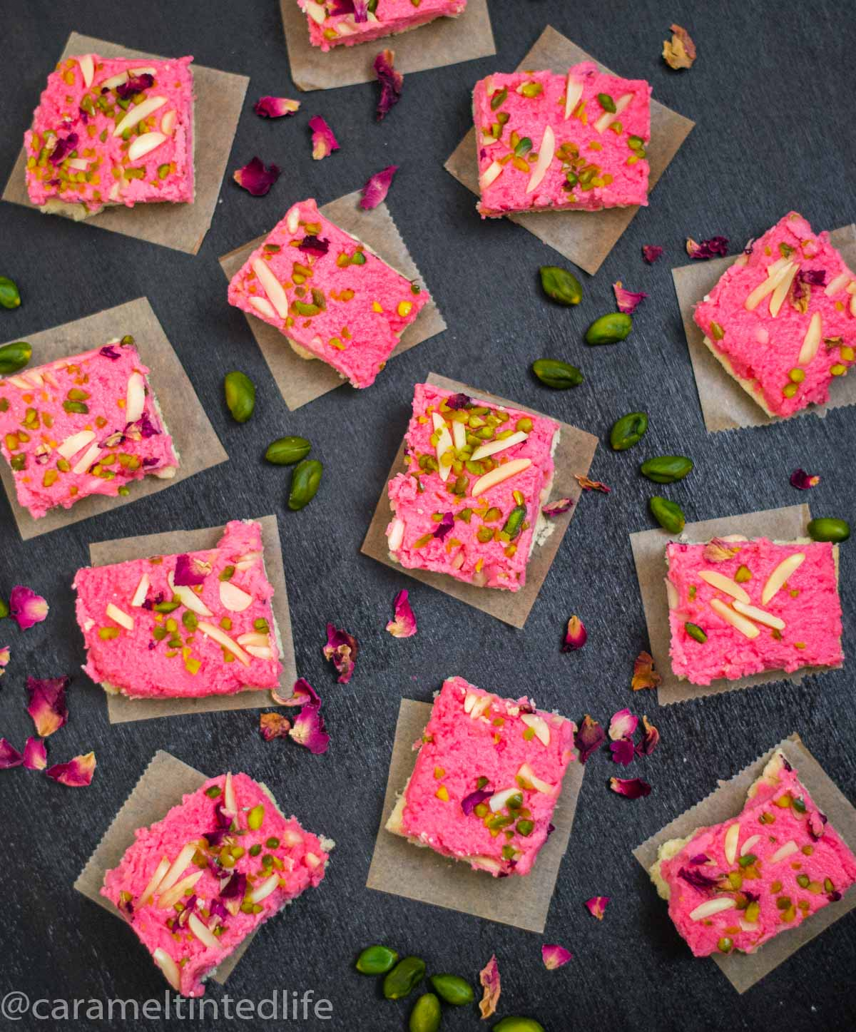 Kalakand squares on a black background viewed from the top, with scattered pistachios and rose petals