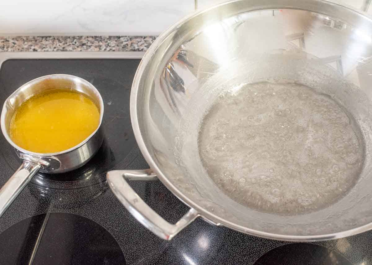 wok with hot sugar syrup mixture next to pot with ghee-oil on the stovetop