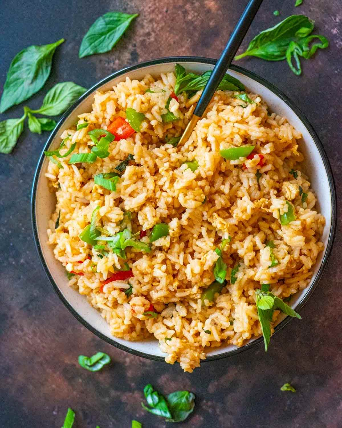 Top view of a bowl of fried rice and a serving spoon placed on a brown board