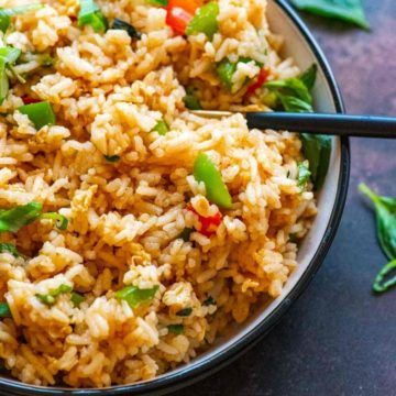 Closeup of a bowl of fried rice garnished with green onions and basil leaves scattered in the background