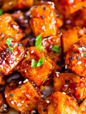 Crispy tofu coated in a sticky Asian sauce with sesame seeds and scallion garnish