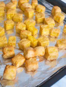 Crispy baked Tofu pieces on a baking sheet