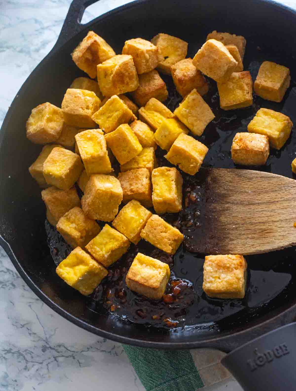 Crispy Tofu added into cast iron pan with Asian sauce