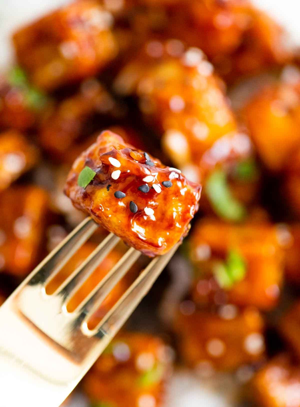 piece of tofu covered in sauce and sesame seeds, on a fork