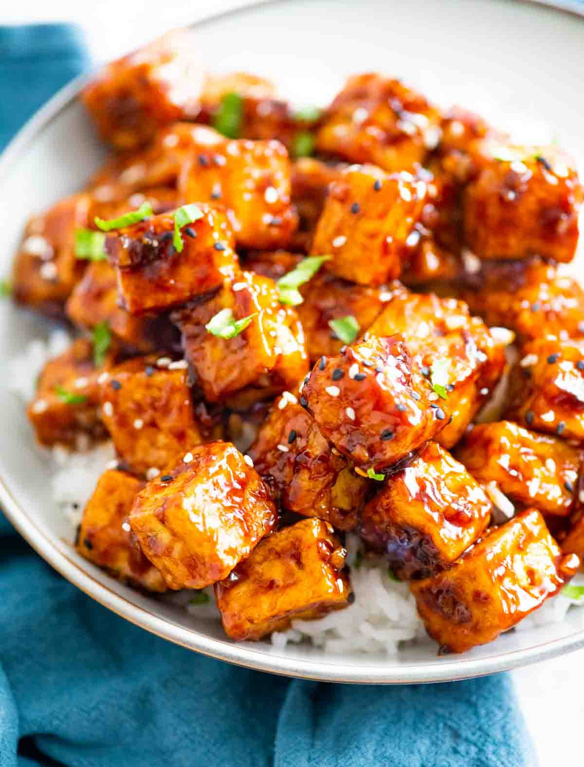 Tofu covered in Asian sauce garnished with sesame seeds in a bowl