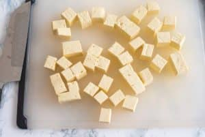 Tofu cut into cubes on a cutting board, next to a knife