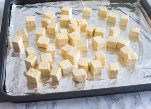 Tofu pieces spread out on a foil on a baking tray