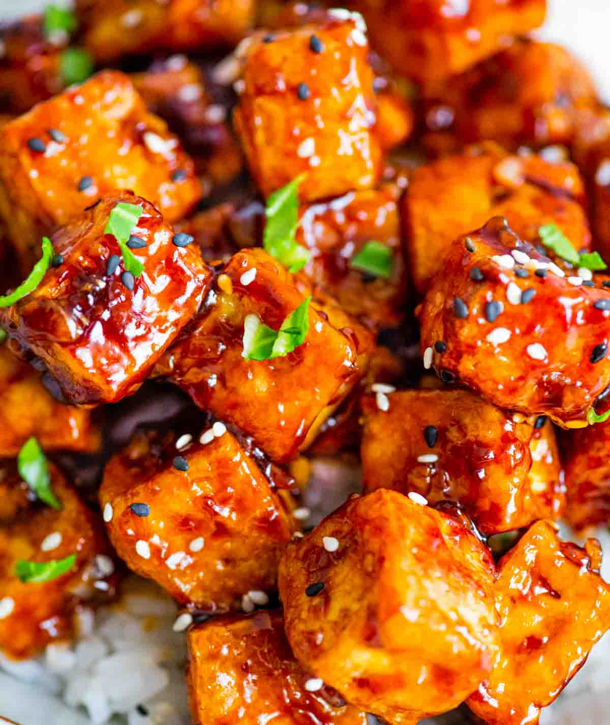 Close up of crispy tofu covered in sauce, garnished in sesame seeds