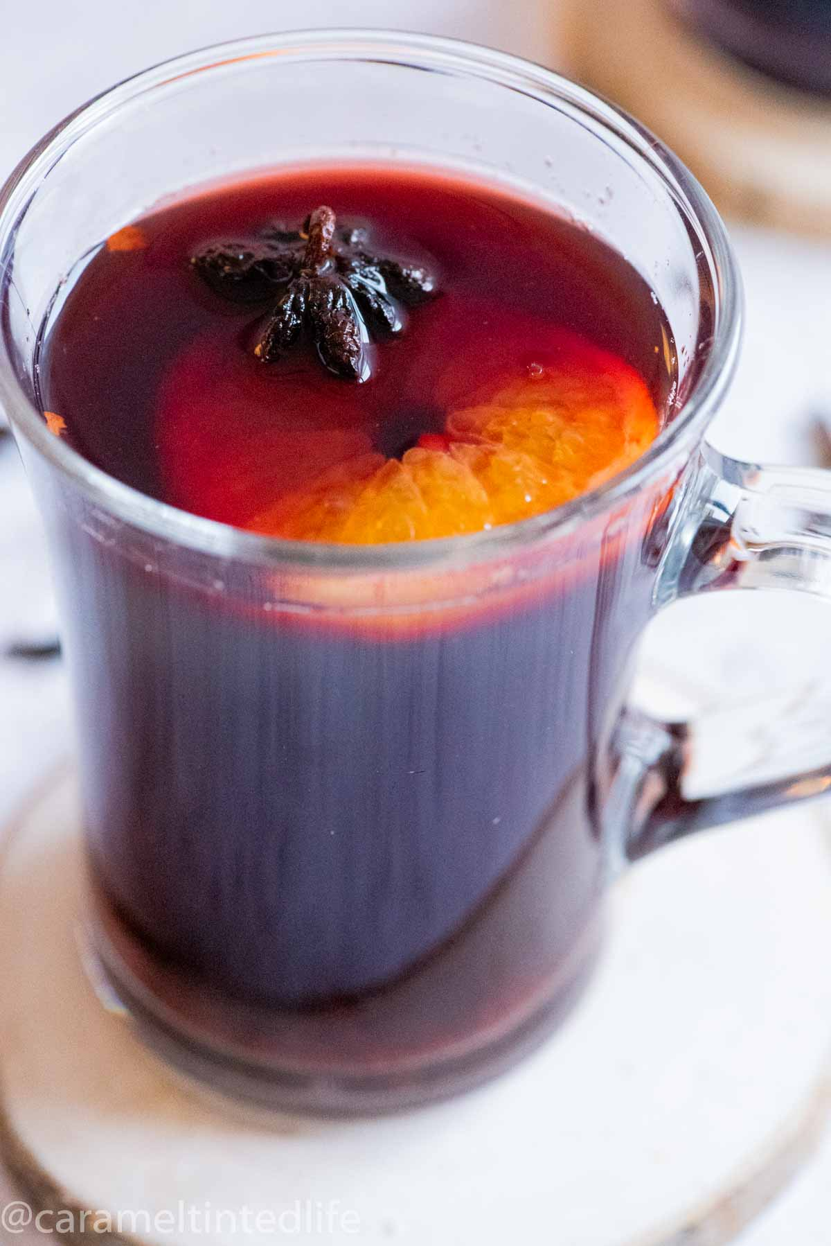 Close up of a glass of mulled wine with a star anise and orange slice