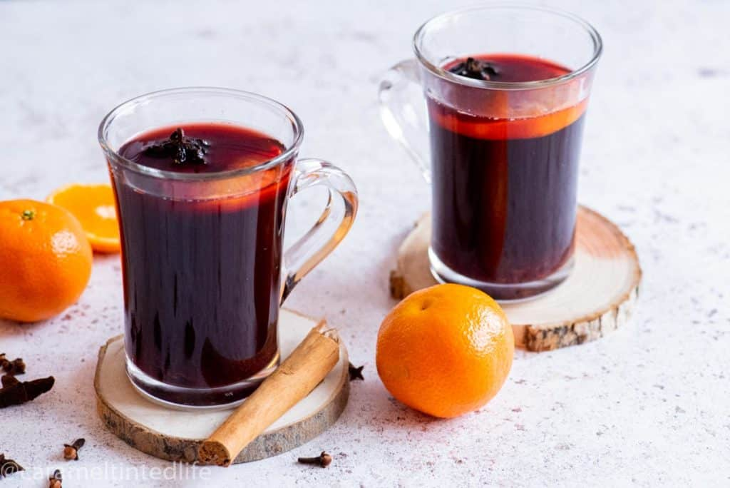 Two glasses of mulled wine resting a wooden coasters
